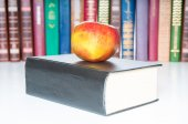 Books with apple on white background — Stockfoto