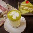 Green tea cake with a cup of hot green tea latte — Stock Photo #70276255