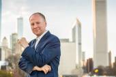 Successful businessman among office buildings. — Stock Photo