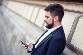 Businessman sending text message with his mobile phone — Foto Stock
