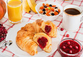 Breakfast with coffee, croissants, juice and fruit. — Stockfoto