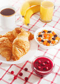 Breakfast with coffee, croissants, juice and fruit. — Photo