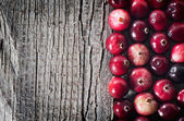 Ripe cranberry on an old wooden board with space for text. — Zdjęcie stockowe