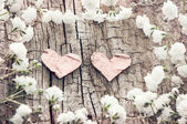 White flowers and two hearts on a wooden background. Romantic ca — Stock Photo
