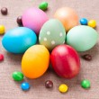 Group of colorful Easter eggs and colored candies lying on linen fabric cloth close up — Stock Photo #68875477
