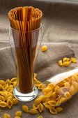 Art still life shell macaroni pasta in glass on hessian linen fabric cloth background — Stock Photo