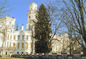 Ancient european white castle standing across green park in blue sky at sunny day — Stock Photo
