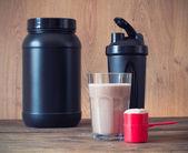 Vassle proteinpulver i scoop och plast shaker på trä bakgrund — Stockfoto