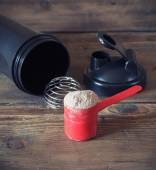 Whey protein powder in scoop and plastic shaker on wooden background — Stock Photo