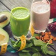 Two fresh blended fruit smoothies made with avocado, pomegranate, spinach and almonds — Stock Photo #71362639