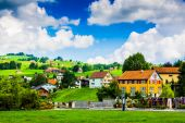 Houses in a little swiss town with clouds and blue sky in backgr — Stock Photo