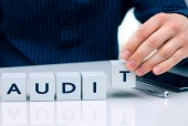 """Businessman arranging small blocks with word """"Audit"""" — Stock Photo"""