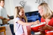 Family: Young Giirl Takes Popcorn From Bowl — Stock Photo