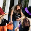 Halloween: Mother Hands Out Candy to Little Girl Witch — Stock Photo #52110703