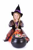 Halloween: Girl Witch Digs Into Pot Of Halloween Goodies — Стоковое фото