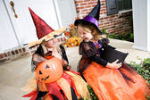 Halloween: Girls Sit On Front Porch With Trick Or Treat Candy — Стоковое фото