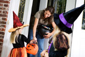 Halloween: Mother Hands Out Candy to Little Girl Witch — Foto de Stock