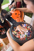 Halloween: Girl Grabs For Halloween Candy From Bucket — Stock Photo