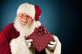 Santa: Holding Up Wrapped Christmas Gift — Stock Photo