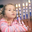 Hanukkah: Little Girl Looks At Lit Hanukkah Candles — Stock Photo #53196381