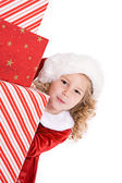 Christmas: Cute Santa Girl Peeks Around Stack Of Gifts — Foto de Stock