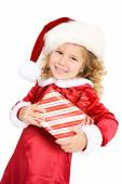 Christmas: Cute Girl In Santa Hat Carrying Gift — Stockfoto