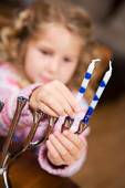 Hanukkah: Cute Girl Puts Candles Into Menorah — Stockfoto