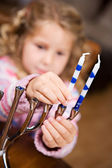 Hanukkah: Cute Girl Puts Candles Into Menorah — Zdjęcie stockowe