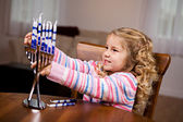 Hanukkah: Little Girl Putting Candles Into Menorah — Stockfoto