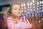 Hanukkah: Little Girl Looks At Lit Hanukkah Candles  — Stockfoto