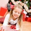 Christmas: Young Girl Looks Down At Wrapped Gift — Stock Photo #56337157