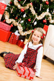 Christmas: Smiling Girl Sits On Floor With Wrapped Gift — Foto Stock