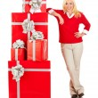 Christmas: Smiling Woman Leans On Stack Of Red Christmas Gifts — Stock Photo #56347385