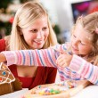 Christmas: Young Girl Uses Candy To Decorate Gingerbread House W — Stock Photo #58696457