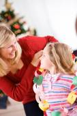 Christmas: Mother Wraps Paper Chain Garland Around Girl — Stockfoto