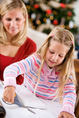 Christmas: Little Girl Cuts Wrapping Paper For Present — Zdjęcie stockowe