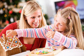 Christmas: Young Girl Uses Candy To Decorate Gingerbread House W — Stockfoto