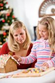 Christmas: Mother And Girl Decorating Gingerbread House Together — Stockfoto