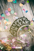 NYE: Fun Party Favors On Confetti And Wooden Background — Stockfoto