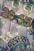 NYE: Glitter 2015 Glasses In Middle Of Party Background — Stockfoto