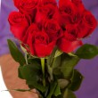 Valentine: Holding Out A Dozen Roses In Bouquet — Stock Photo #61768983