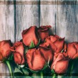 Valentine: Grunge Overhead Of A Dozen Roses On Wood Background — Stock Photo #61770231
