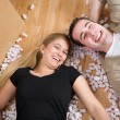 Moving: Couple Laying On Floor Amid Packing Peanuts — Stock Photo #68270487