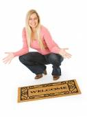 Moving: Woman Posing With Welcome Mat — Stock Photo