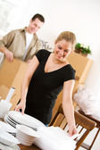Moving: Woman Moving Delicate Plates — Stock Photo
