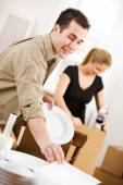 Moving: Wrapping Dishes In Protective Cover — Stock Photo