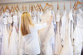 Bride: Woman Browsing Through Rack Of Wedding Gowns — Stock Photo
