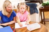 Uczeń: Mała dziewczynka odrabiania lekcji z pomocą rodziców — Zdjęcie stockowe