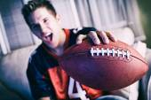 Football: Man Cheering For Team On TV And Holding Out Ball — Stock Photo