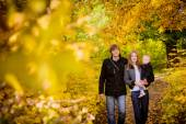 Family with child walking in the autumn park — Stock Photo